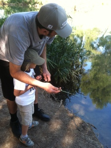 Getting some pointers from his dad before he gets ready to cast his line.