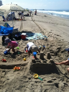 A beach trip is not complete without building sandcastles. And everyone was hard at work, but as you can tell I didn't dress my kid. Pink would never have been an option for my daughter. In fact I have no idea how this swimsuit made it. It's a good thing the Pacific Ocean had magical mood changing powers.